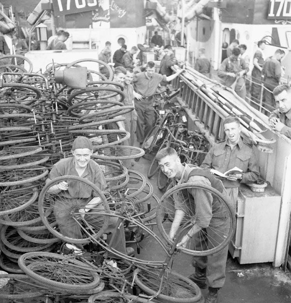 Infantrymen checking bicycles aboard an LCI(L) of the 2nd Canadian (262nd RN) Flotilla. Southampton, England, 6 June 1944. (L-R): Privates Reg Martin and Rodney MacNeill, both of The Lorne Scots (Peel, Dufferin and Halton Regiment); Private George Banning of The Cameron Highlanders of Ottawa (M.G.). Date: 6 June 1944 Place: Southampton, England, Extent: 1 photograph ; 2 1/4 sq. in. Negative Film B/W - safety film Terms of use Credit: Lt Gilbert Alexander Milne / Canada. Dept. of National Defence / Library and Archives Canada / PA-136999